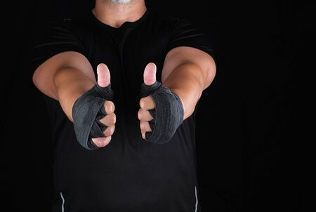 sportsmans hands wrapped in black elastic sports bandage show a like sign, dark background