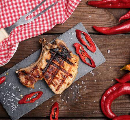 piece of fried pork tenderloin on a bone lies on a black board, juicy meat, close up Фото со стока - 133676988