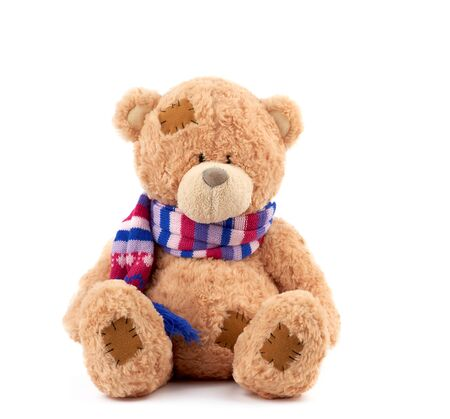 cute brown teddy bear with patches in a colored knitted scarf sitting on an isolated white background, close up Stockfoto
