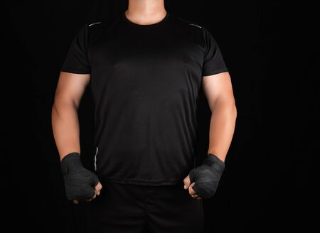 adult athlete in black uniform is standing in a rack with strained muscles, his hands are wrapped in a black textile bandage, dark background