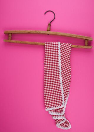 red checkered kitchen towel hanging on a vintage wooden hanger, pink background Фото со стока - 133677013