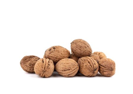 pile of inshell walnuts isolated on a white background, autumn harvest