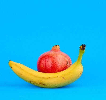 red round ripe pomegranate and yellow bananas in a peel on a blue background
