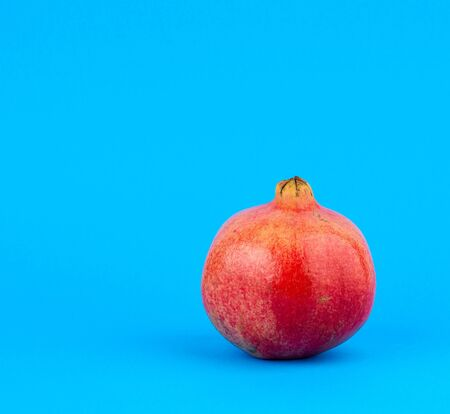 ripe red pomegranate in a peel on a blue background, close up