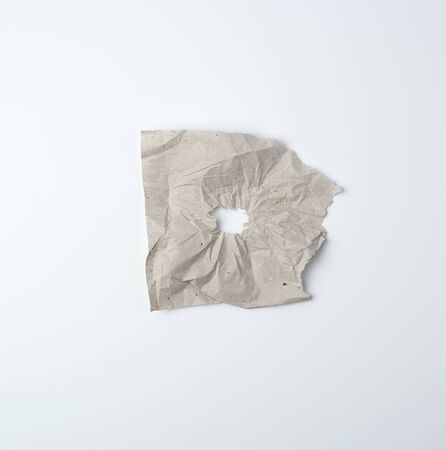 gray crumpled sheet of paper with a hole, white backing, abstract background