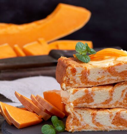 stack of square pieces of baked cheesecake cottage cheese with pumpkin and fresh pieces of vegetable