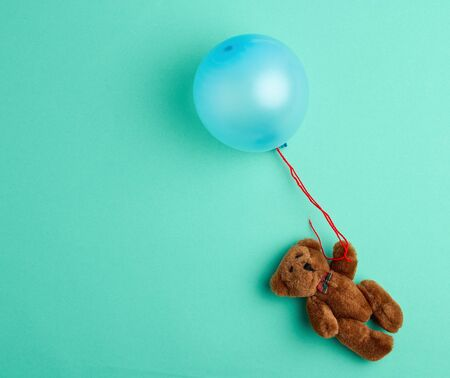 little brown teddy bear holding a pink inflated balloon on a rope on a green background