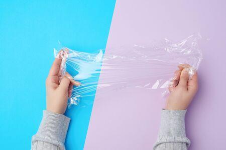 Zwei Hände halten ein Stück transparente Plastikfolie auf farbigem Hintergrund, Draufsicht Standard-Bild