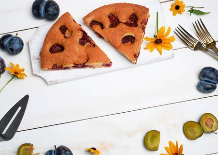 slices of biscuit plum cake on a white wooden board and fresh fruits, top view