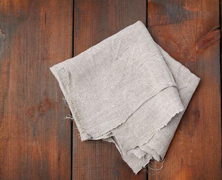 asciugamano di lino grigio piegato su sfondo di legno, vista dall'alto, spazio di copia
