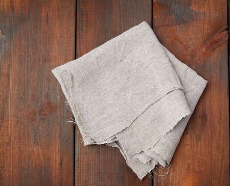 folded gray linen towel on wooden background, top view, copy space