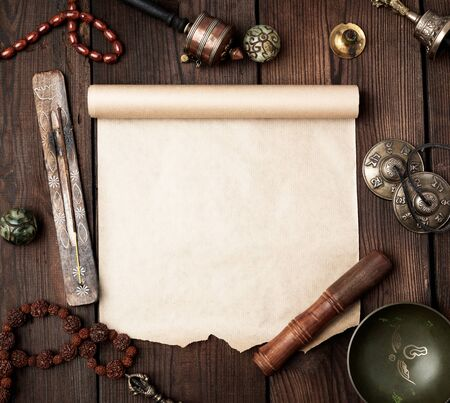 tibetan religious objects for meditation and alternative medicine, empty brown sheet of paper on a brown  wooden background, top view, copy space
