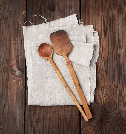wooden old spoon and spatula on a gray linen napkin, top view