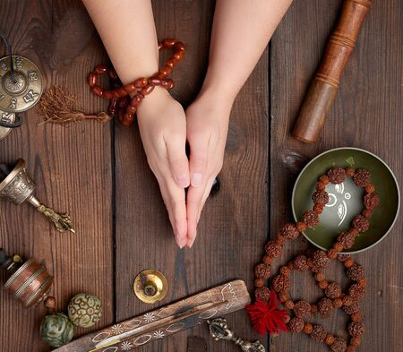 two hands in a prayer pose on a wooden brown table in the middle of vintage Tibetan meditation tools, alternative medicine, top view 스톡 콘텐츠