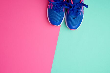 pair of sports sneakers with blue laces on a colored abstract background, copy space Stock Photo