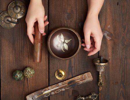 female hands hold a copper Tibetan singing bowl and a wooden stick, on the wooden table are items for alternative medicine, sound massage and meditation 스톡 콘텐츠