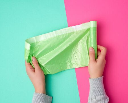 female hand unwinds a green plastic bag for rubbish, green pink background
