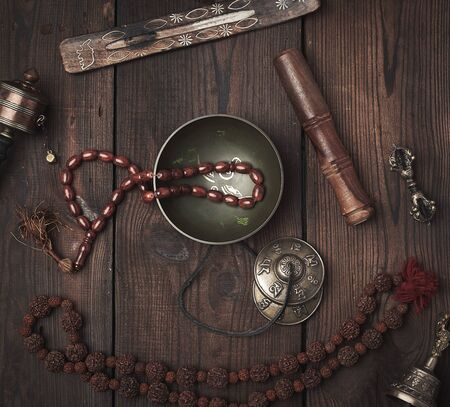 Copper singing bowl, prayer beads, prayer drum and other Tibetan religious objects for meditation and alternative medicine on a brown wooden background 스톡 콘텐츠