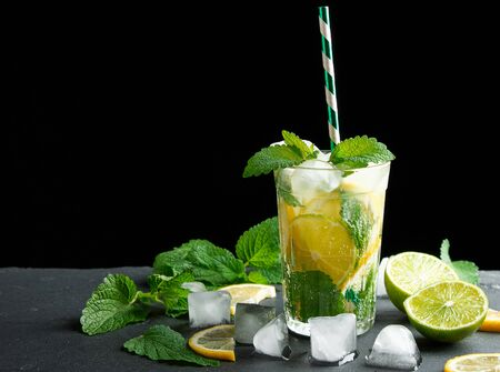 summer refreshing drink lemonade with lemons, mint leaves, ice cubes and lime in a glass on a black background, copy space