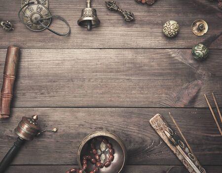 Cuenco de cobre, cuentas de oración, tambor de oración y otros objetos religiosos tibetanos para la meditación y la medicina alternativa sobre un fondo de madera marrón