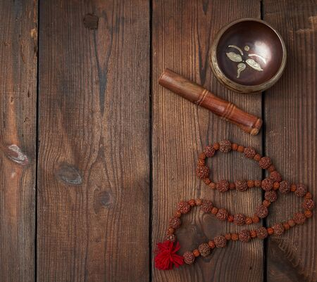 singing Tibetan copper bowl and wooden stick on a table of brown boards, top view, copy space