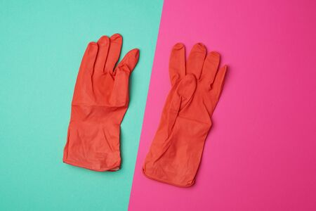pair of rubber orange gloves for cleaning the house on a colored background, flat lay