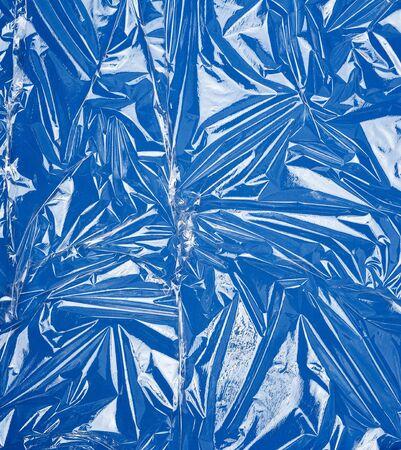 Textur einer transparenten Stretchfolie zum Verpacken von Produkten auf blauem Hintergrund, Vollbild, Nahaufnahme