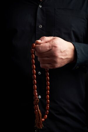 man in a black shirt holds a brown stone rosary in his left hand,  low key. used to count prayers or other ritual actions, to preserve attention and concentration, to set the rhythm