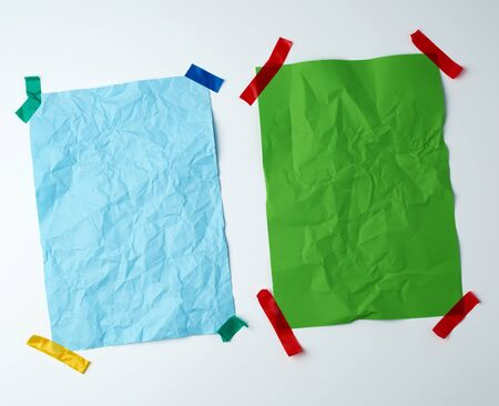 two blank crumpled sheets of paper glued with rubber colored adhesive tape on a white background, copy space Imagens