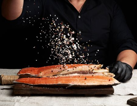 le chef en chemise noire et gants en latex noir prépare un filet de saumon sur une planche à découper en bois, processus de saupoudrage d'épices et de sel, discret Banque d'images