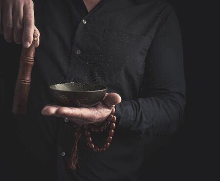 man in a black shirt rotates a wooden stick around a copper Tibetan bowl of water. ritual of meditation, prayers and immersion in a trance. Alternative treatment Stock fotó