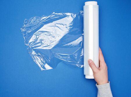 Hand halten Sie eine große Rolle gewickelter weißer transparenter Folie zum Verpacken von Lebensmitteln, Draufsicht, blauer Hintergrund