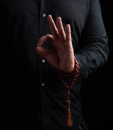 man in a black shirt shows with his left hand the gian mudra, concept of meditation and relaxation