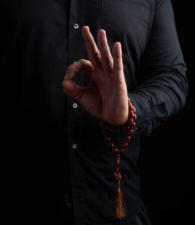 Mann in einem schwarzen Hemd zeigt mit seiner linken Hand das Gian Mudra, Konzept der Meditation und Entspannung