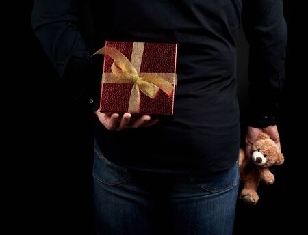 adult man in a black shirt and blue jeans holds a red gift box with a bow behind him, concept of surprise