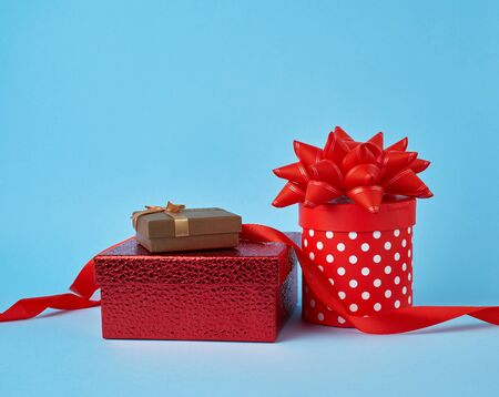stack of wrapped gifts with knotted bows on a blue background, festive backdrop