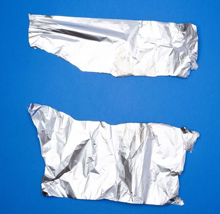 two torn silver pieces of baking foil on a blue background, creased parts with uneven edges