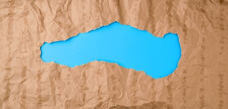 crumpled paper texture from a brown sheet of paper with greasy spots and a large hole. abstract banner for the designer, blue backdrop.