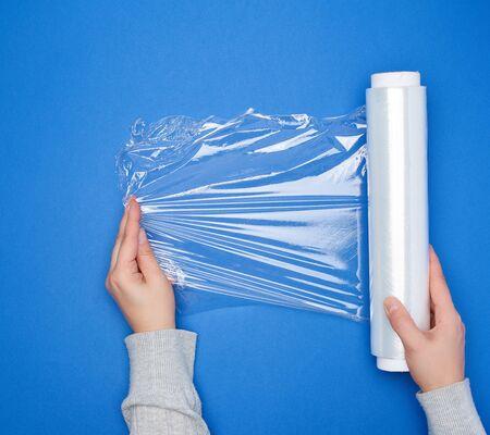 Tenir à la main un grand rouleau de film transparent blanc enroulé pour emballer les aliments, vue de dessus, fond bleu