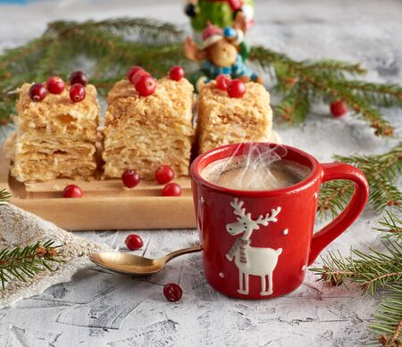 red ceramic cup with black coffee and slices of puff cake Napoleon with butter cream decorated with cranberries, festive backdrop