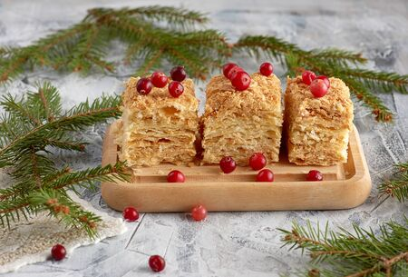 pieces of baked layer of cake Napoleon with butter cream on a wooden board, close up