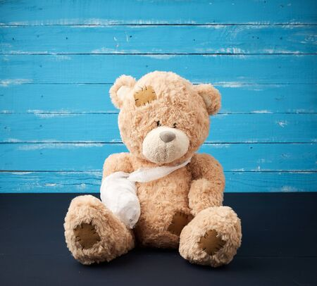 big brown teddy bear with rewound white bandage paw on a blue wooden background, pediatrics concept