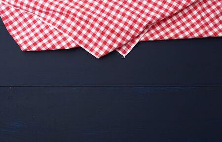 weißes rot kariertes Küchentuch auf blauem Holzhintergrund, Picknickhintergrund, Kopienraum