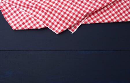 white red checkered kitchen towel on a blue wooden background, picnic background, copy space