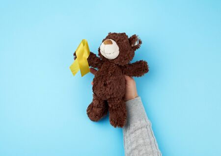 female hand hold a small brown teddy bear which holds in its paw a yellow ribbon folded in a loop on a blue background. concept of the fight against childhood cancer. problem of suicides