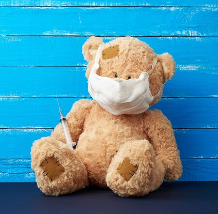 beige big teddy bear with patches sitting in a white medical mask in the paw of a syringe, concept of the need for vaccinations in children, blue wooden background. Injection, vaccine concept.
