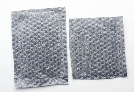 fragment of a transparent film with air for the transportation of parcels is glued on gray polyethylene on a white background, inside of the envelope Stockfoto