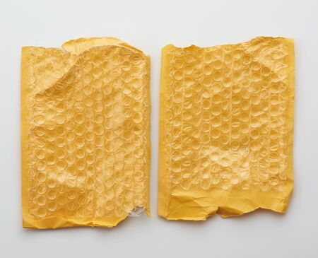 fragment of a transparent film with air for transportation of parcels is glued on a yellow sheet of paper, inside of the envelope on a white background