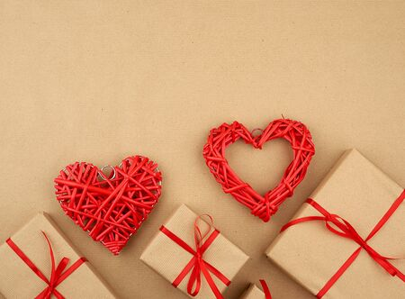 gift wrapped in brown kraft paper and tied with a thin silk ribbon on a background of paper, top view. Congratulations on Valentine's Day February 14, copy space Stock Photo - 137467676