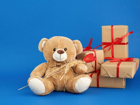 small beige teddy bear and a stack of boxes wrapped in brown kraft paper and tied with a red ribbon, blue festive backdrop for Valentine's Day and birthday